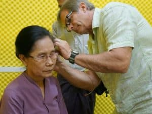 Man gives a woman an hearing exam