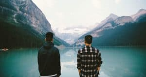 Two men looking at lake with mountains