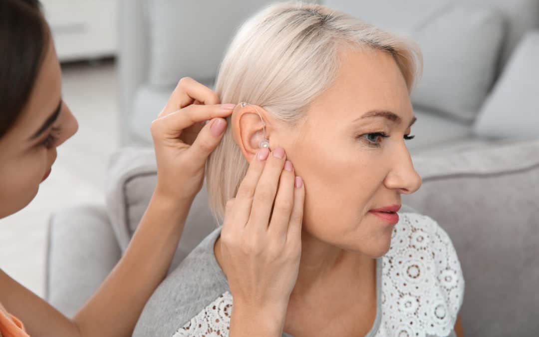 Putting Hearing Aid In Mothers Ear